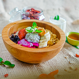 A healthy breakfast with toasted muesli, rice crispy, cornflakes, and yogurt served on wooden bowl