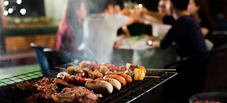 meat and sausages are grilled at outdoor bbq party