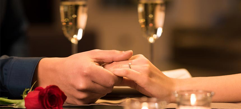 romantic moment between man and woman at a candle light dinner