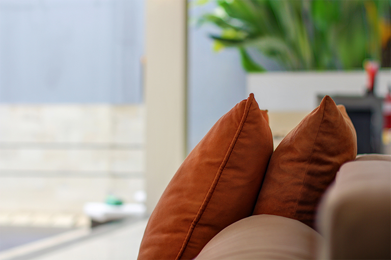 Comfy orange cushions matched on sofa at living room