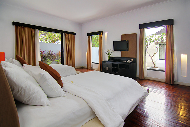 Twin bedroom with garden view and TV furniture.