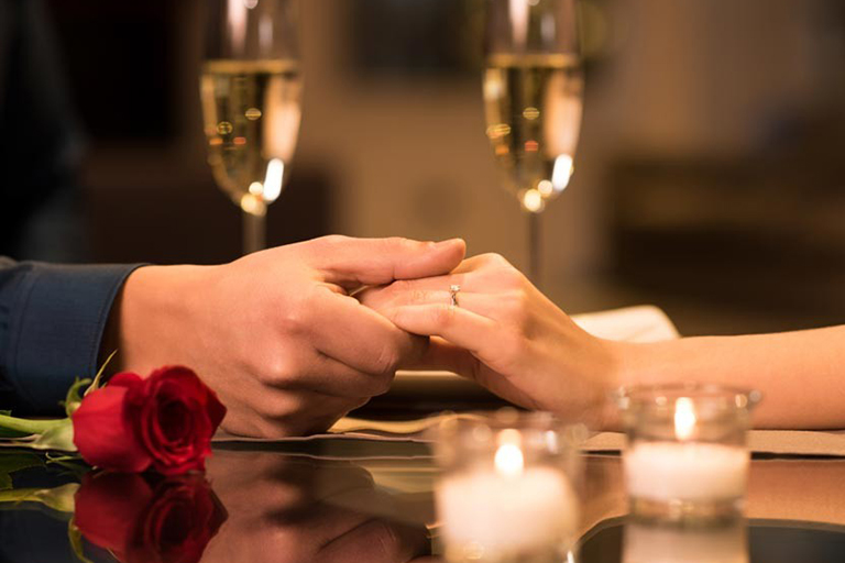 Couple holding hands on their candlelight dinner date