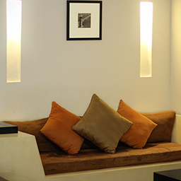 Comfy sofa with orange colored cushions at living space in the bedroom