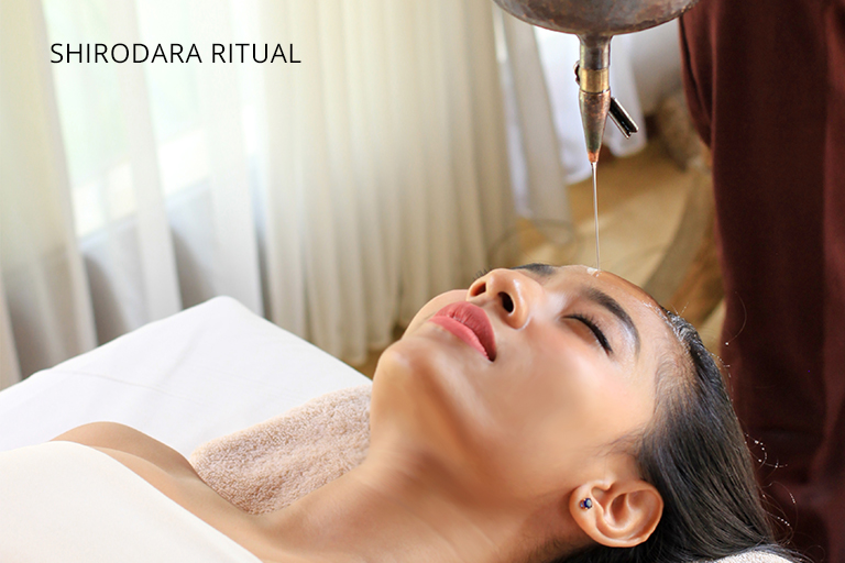 Girl is indulged by a gentle flowing oil on her forehead during Shirodhara treatment