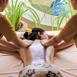 Girl gets Lomi lomi massage appliead by two therapists