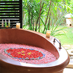 A bath tub is full of frangipani and rose petals for flower bath ritual
