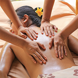 Girl enjoying four hands massage therapy applied by two therapist