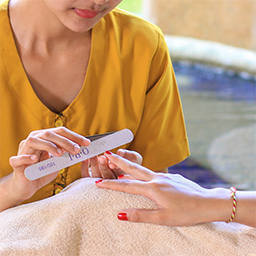 Therapist gives a manicure treatment to a lady