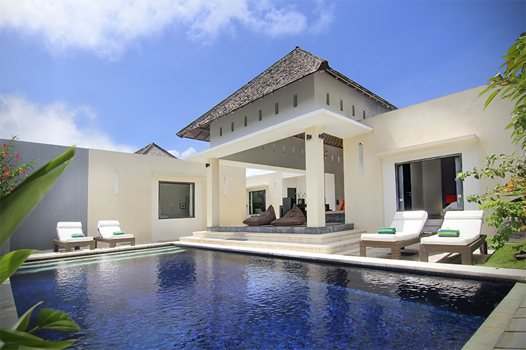 Beautiful front view of villa with large private pool area in afternoon
