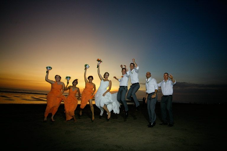 Bridesmaids, best men, groom, and bride in a fun jumping style during wedding photoshot